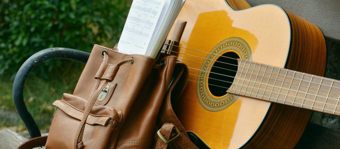 brown-acoustic-guitar-beside-brown-leather-bucket-backpack-164697